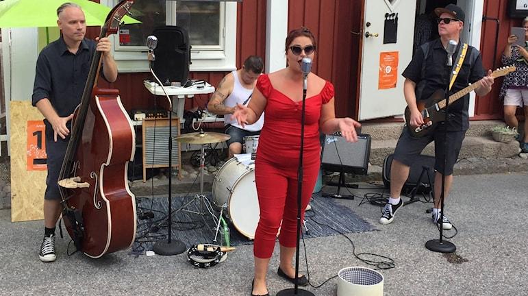 En man som spelar ståbas, en trummis en sångerska i rött och en gitarrist.
