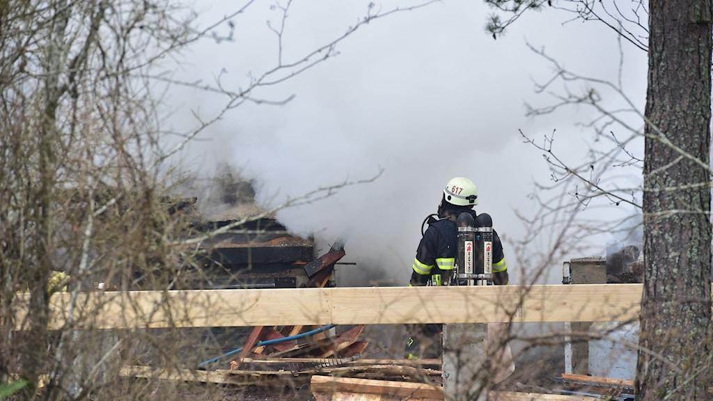 brandman och rök från byggnad.