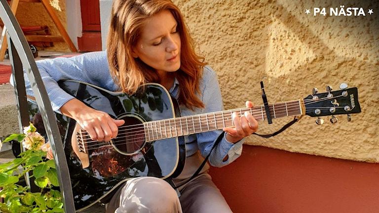 Linnéa Lindgren med gitarr.
