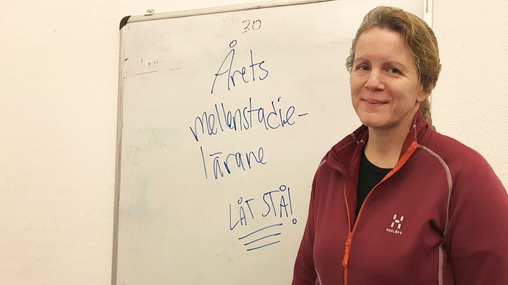 """Kerstin Dahlin står framför en whiteboard med texten """"årets mellanstadielärare""""."""
