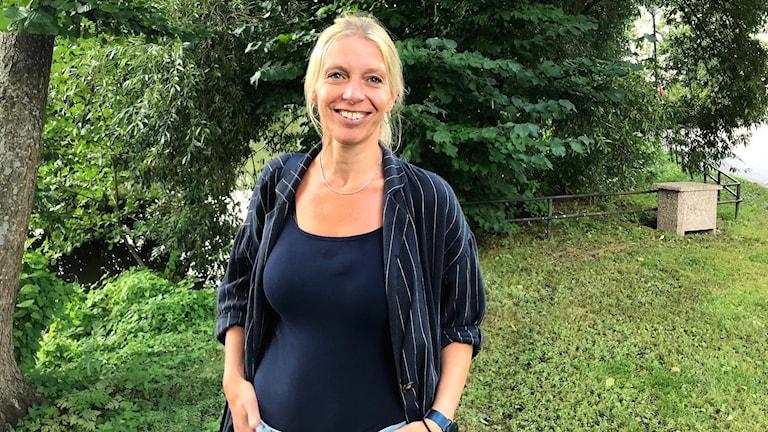 Åsa Johansson, antikvarie Sörmlands museum, framför grönskande bakgrund.