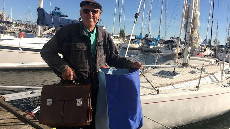 Sven Östensson med portfölj och segelsäck på bryggan framför sin segelbåt.