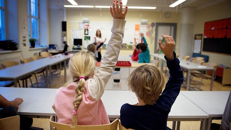 Två lågstadieelever i årskurs 2 räcker upp handen under en lektion i Sofia skola