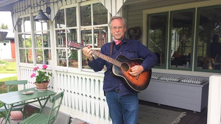 James håller en gitarr