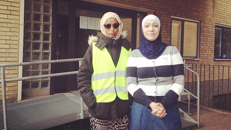 Två kvinnor står framför skola