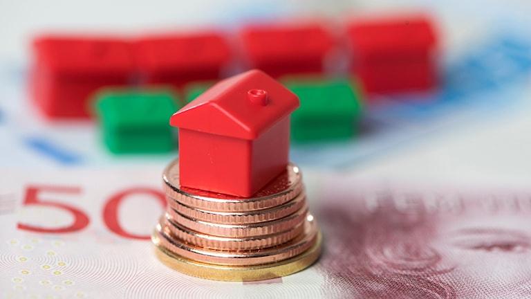 Bild på hus på en trave pengar