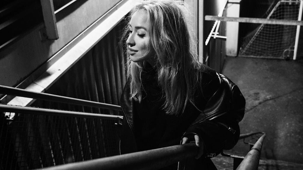 Artisten NEA EINI går upp för en trappa. Bilden är svartvit.
