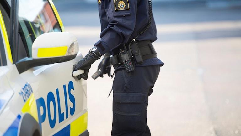 En polis öppnar dörren till sin polisbil. Foto: Fredrik Sandberg/TT.