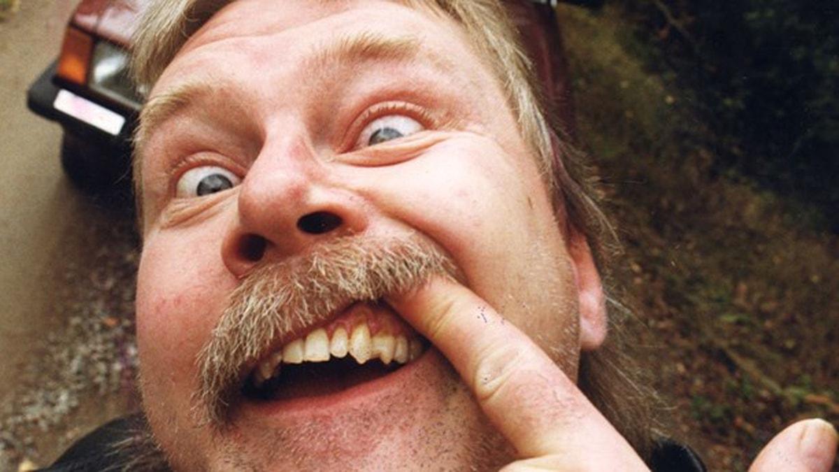 """Eddie """"Medusa"""" Medza kör upp ansiktet mot kameran med en vild blick och ett finger upp i snushålan i munnen."""