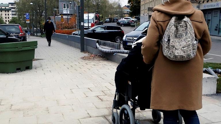 En person i rullstol får hjälp av en assistent.