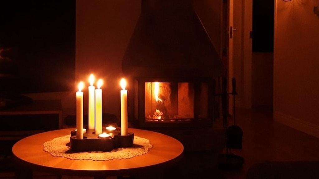 Tända ljus på ett bord och en kakelugn med eld i bakgrunden.