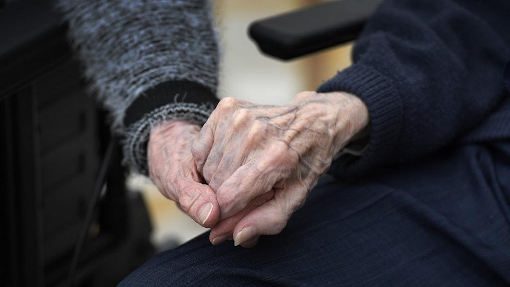 Två äldre håller handen.