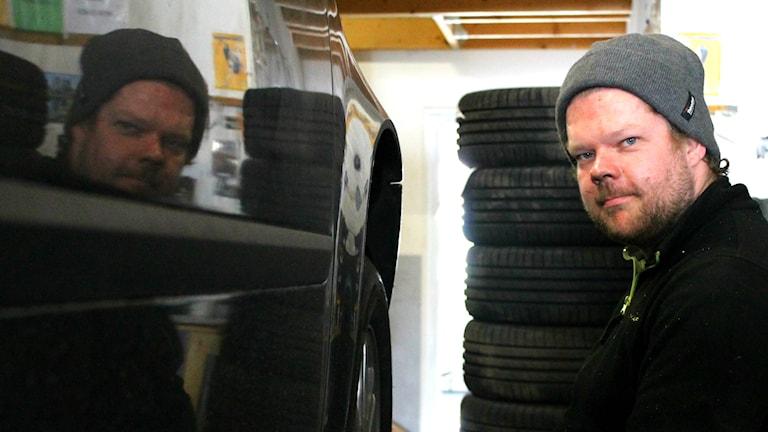 Mattias Landin vid en bil, i bakgrunden uppstaplade däck.