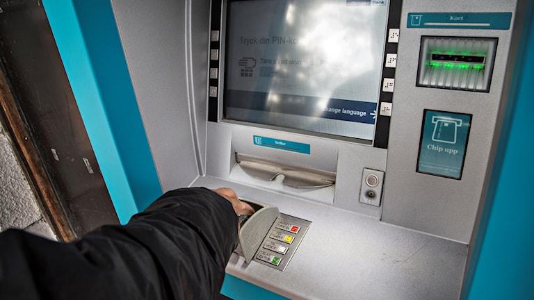 En person tar ut pengar från en bankomat.