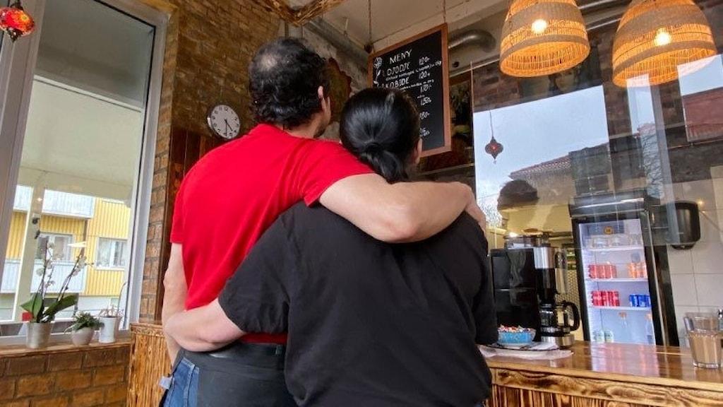 Två personer står i en restaurang med ryggarna vända mot kameran.