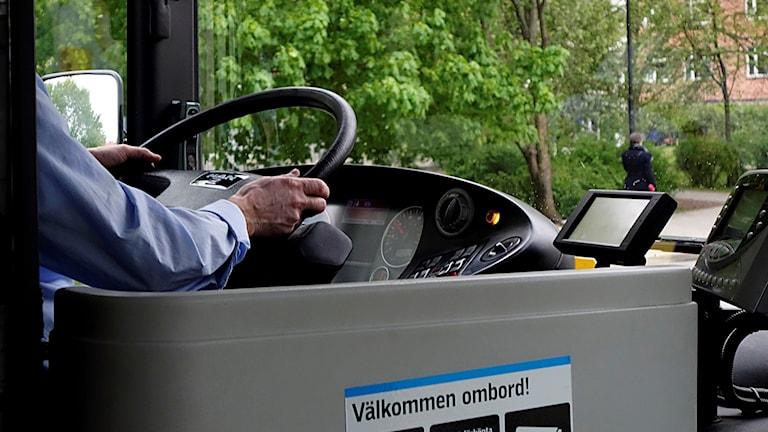 En person sitter vid ratten på en buss.