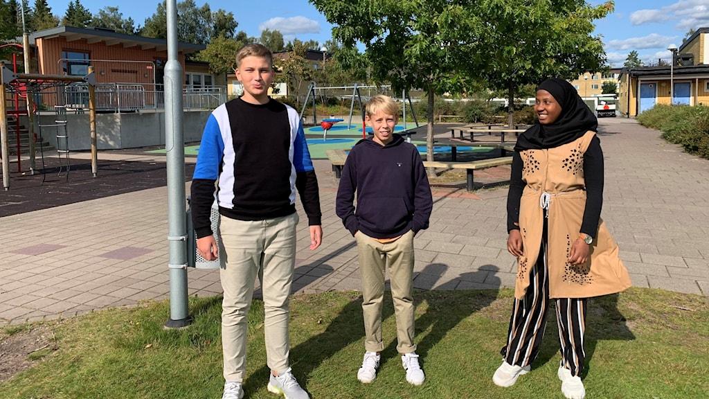 Tre sjätteklassare på en skolgård.