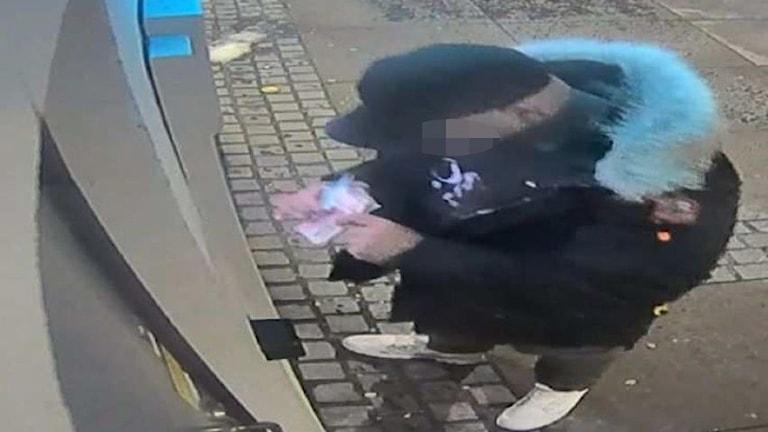 Misstänkt bedragare tar ut kontanter i en bankomat.