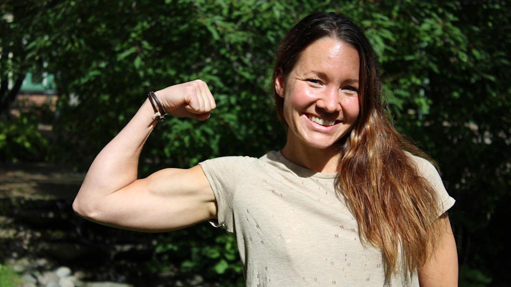 Eva Sederholm spänner sin överarm och ler.