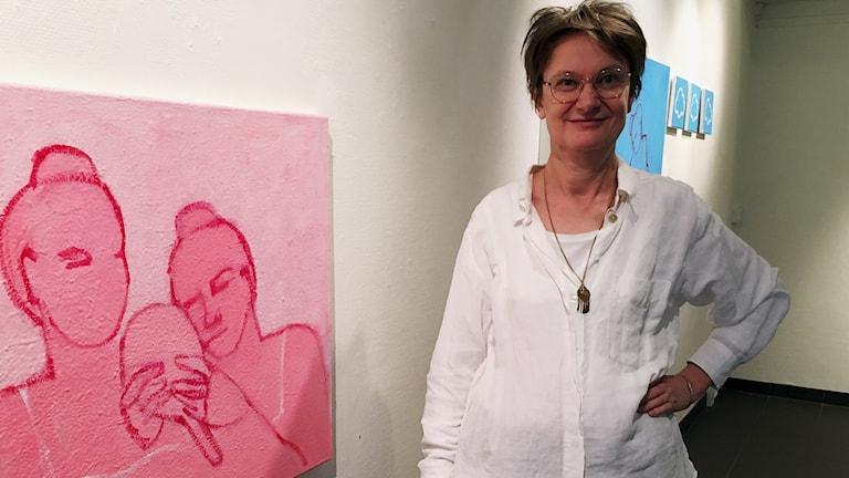 En kvinna står bredvid en rosa tavla med motivet av två människor som håller i en handspegel.