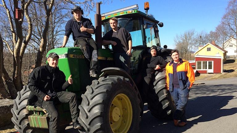 Fem elever på naturbruksgymnasiet står vid en traktor.