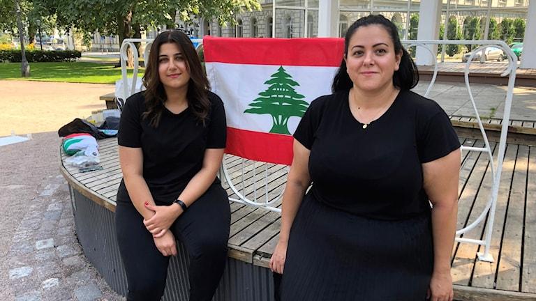 Michella Sayat och Cynthia Esber sittandes på kanten på scenen med den libanesiska flaggan bakom sig.