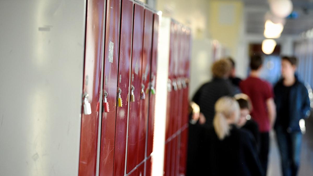 En skolkorridor med elever och skåp.