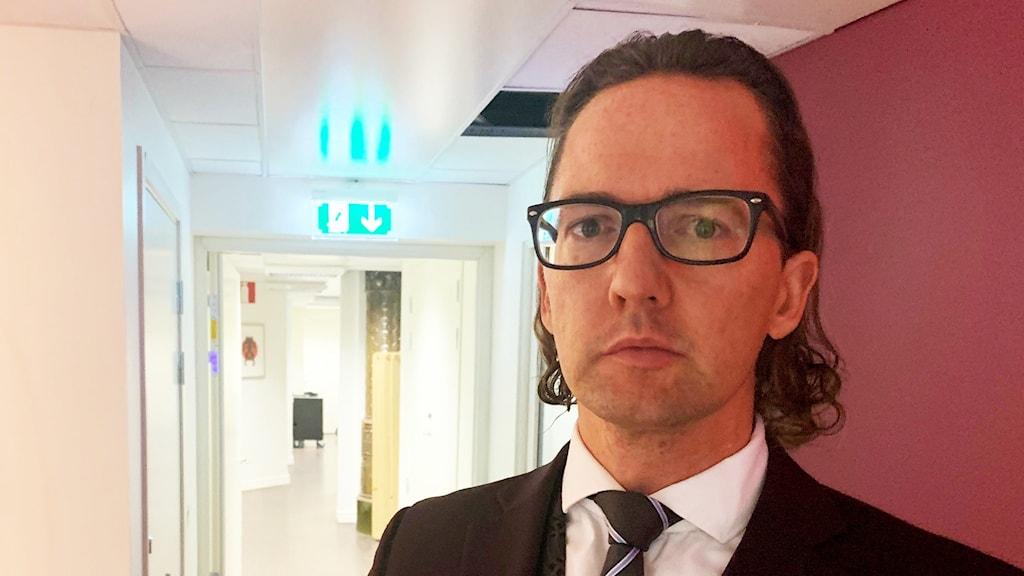 En man i svart kostym och svarta glasögon står inne i en lokal med lila väggar.