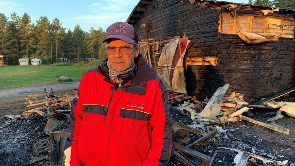 Bild på Anders Stein framför receptionshuset som är svart av branden.