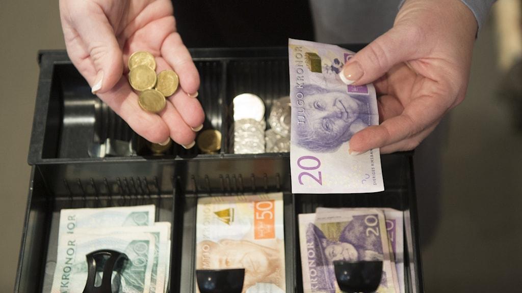 Händer plockar upp pengar ur kassaapparat.