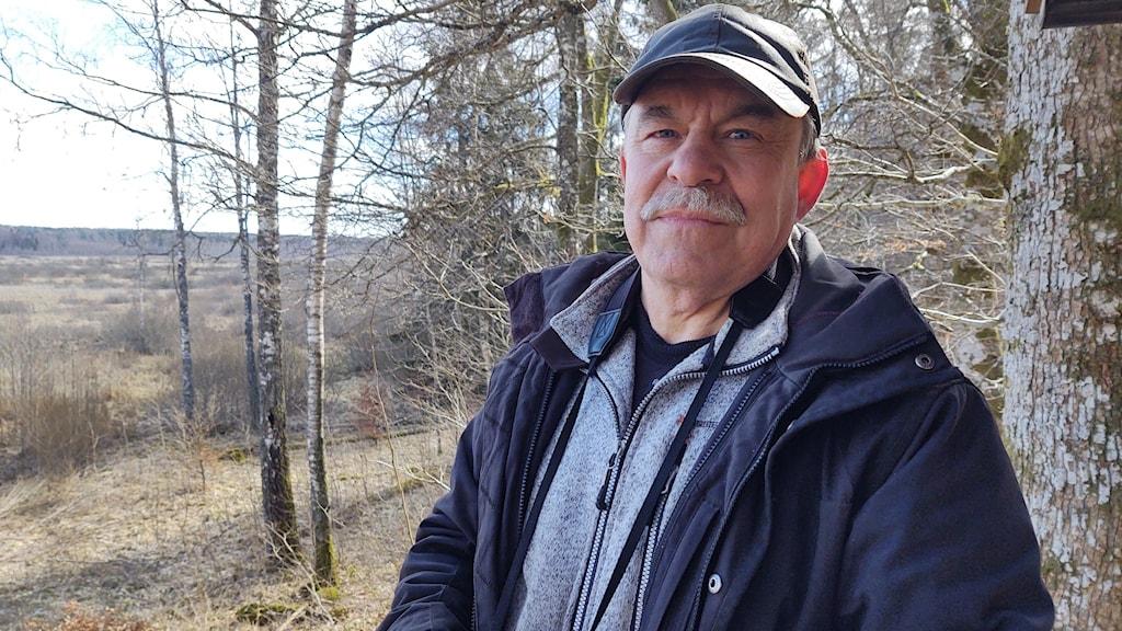 En man står med en kikare och kollar på naturen.