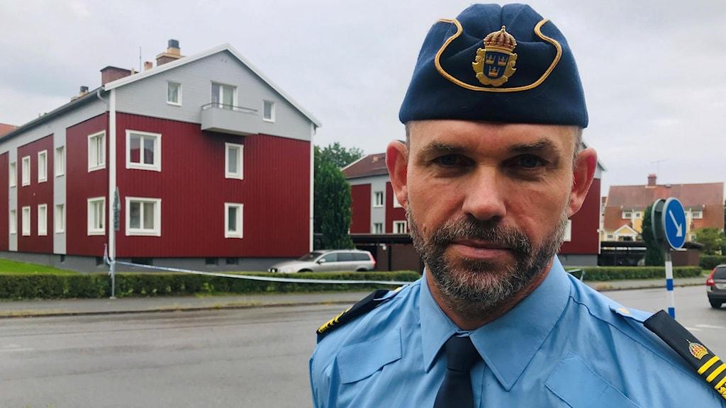 Rickard Finndahl från polisen framför avspärrningsband. I bakgrunden huset, rött, där brottet ska ha ägt rum.