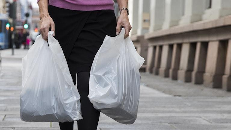 Kvinna med plastpåsar