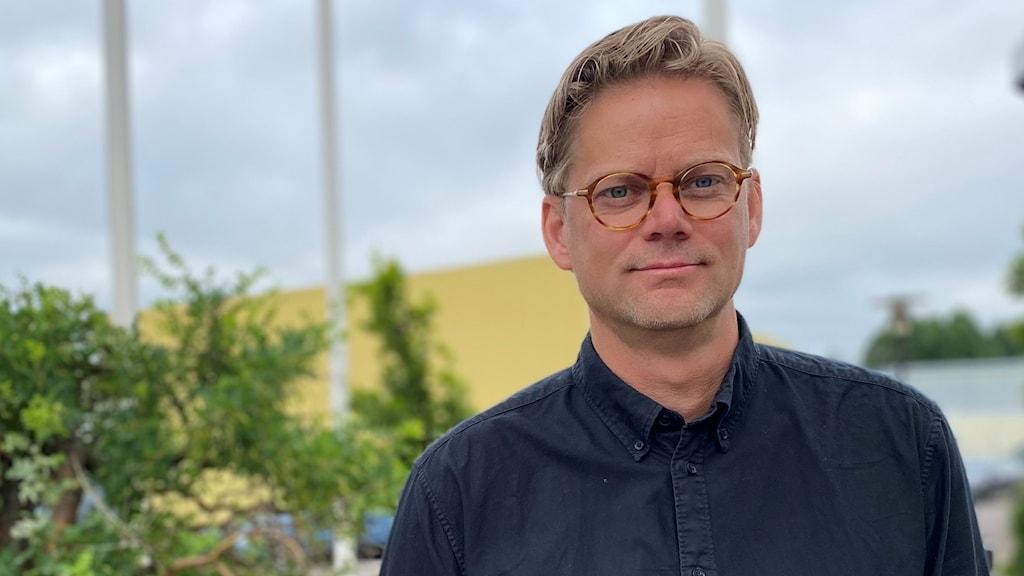 En man i glasögon med blå skjorta.