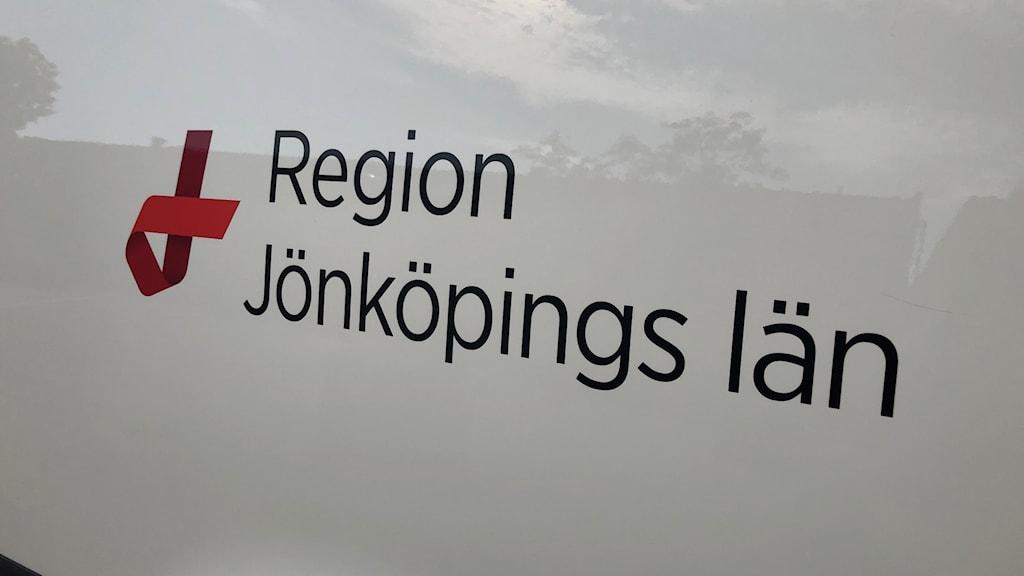 """En vit skylt där det står """"Region Jönköpings län"""" med svarta bokstäver."""