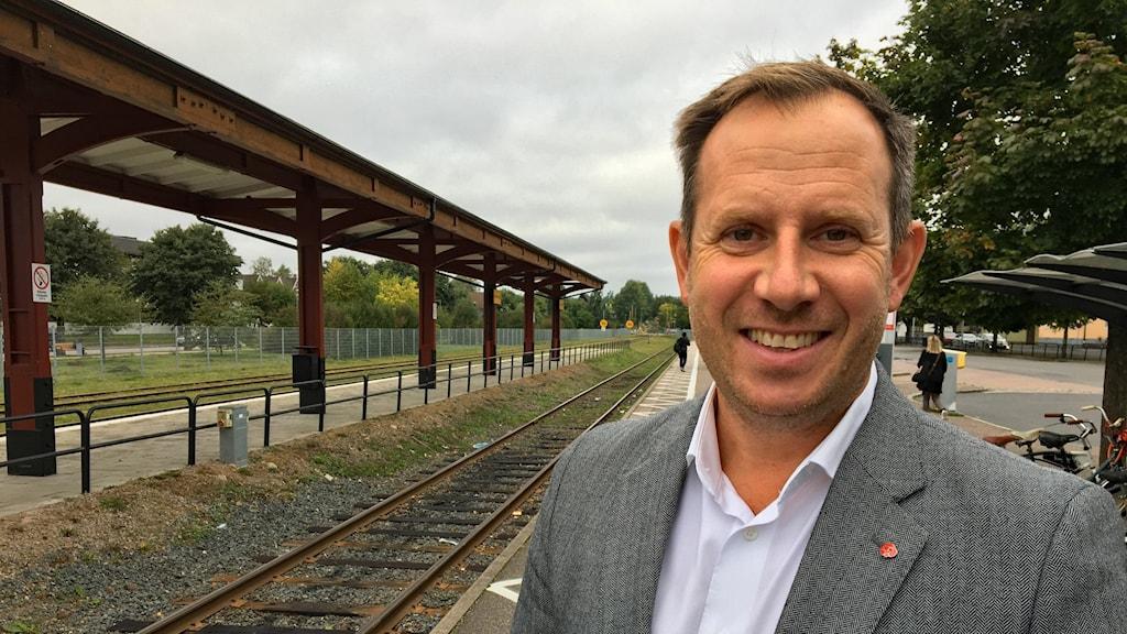 Henrik Tvarnö, socialdemokratiskt kommunalråd står vid järnvägsstationen i Vetlanda med perrongen bakom sig.