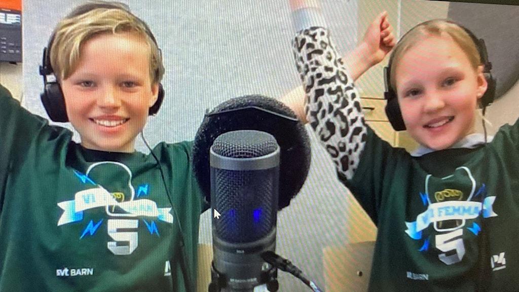 Två glada barn framför en mikrofon