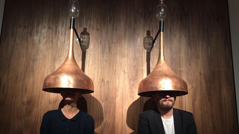 Två personer har varsin stor kopparfärgad tratt över huvudet.