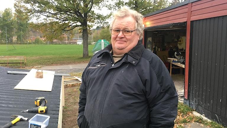 Man i svart jacka står framför verktygsbod i utomhusmiljö.