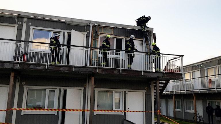 Brandmän står utanför en lägenhet på andra våningen där en lägenhet är utbrunnen.