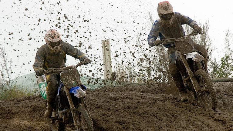 Två motocrossåkare på lerig bana.