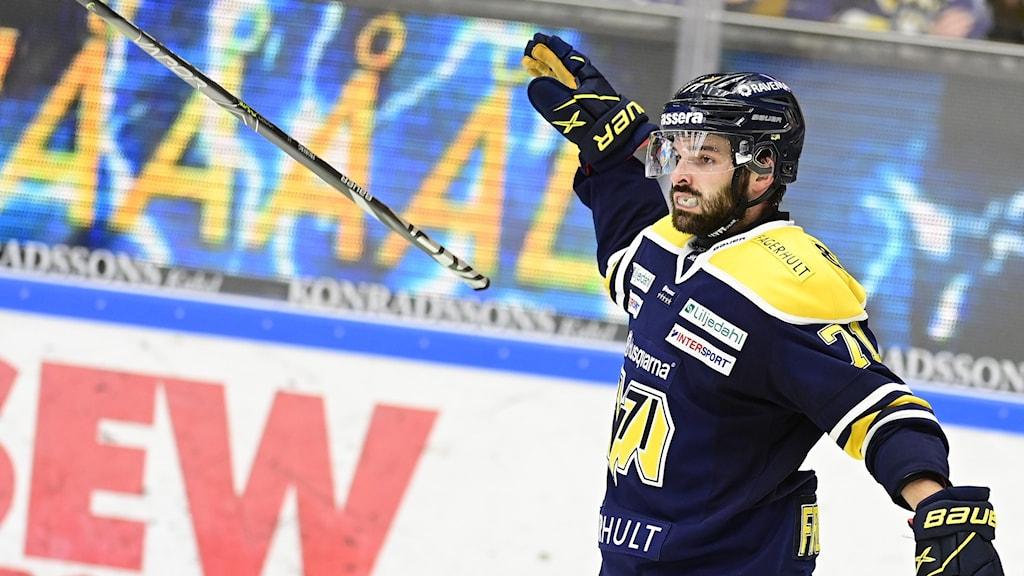 En ishockeyspelare jublar och kastar sin klubba med sargen i bakgrunden.