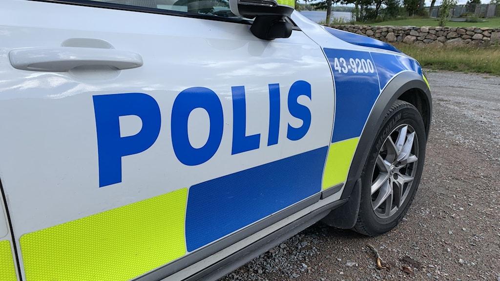 """Framdörren på passagerarsidan på en polisbil parkerad på en landsväg, där det står """"polis"""" i stora blå bokstäver."""