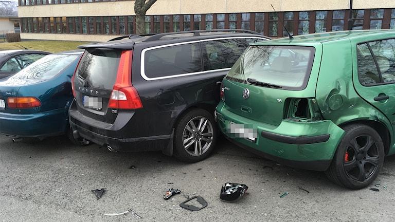 Tre bilar står väldigt tätt på en parkering. Bilarna är buckliga och det ligger bildelar på marken.