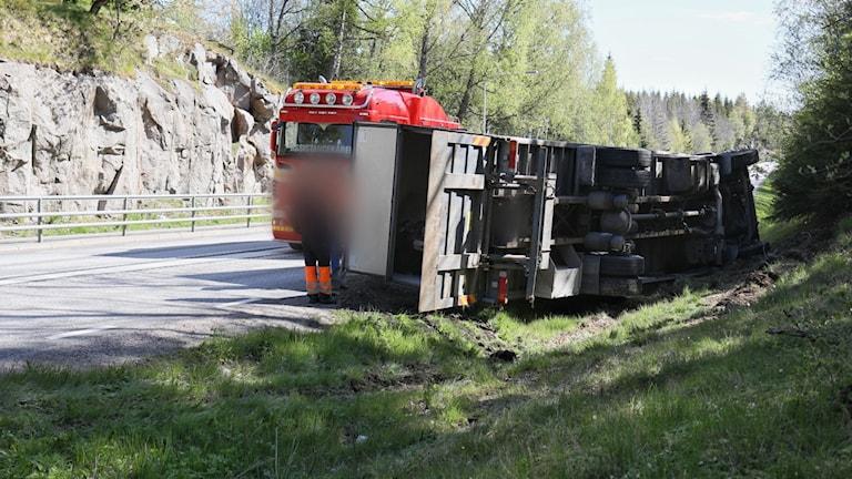 En lastbil ligger på sidan i diket