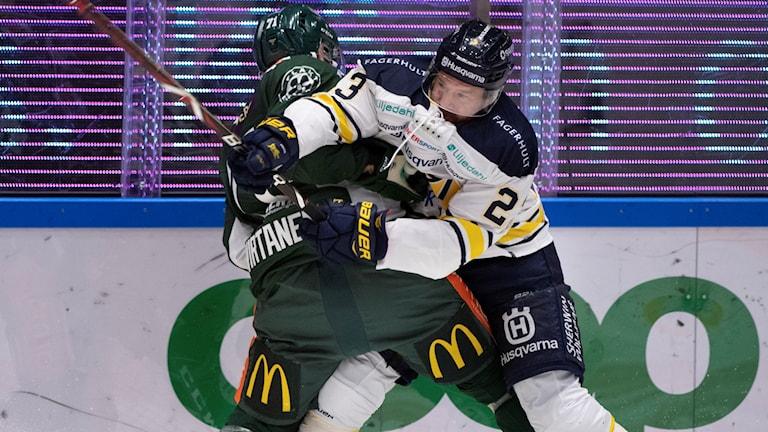 Två hockeyspelare som tacklas på isen.