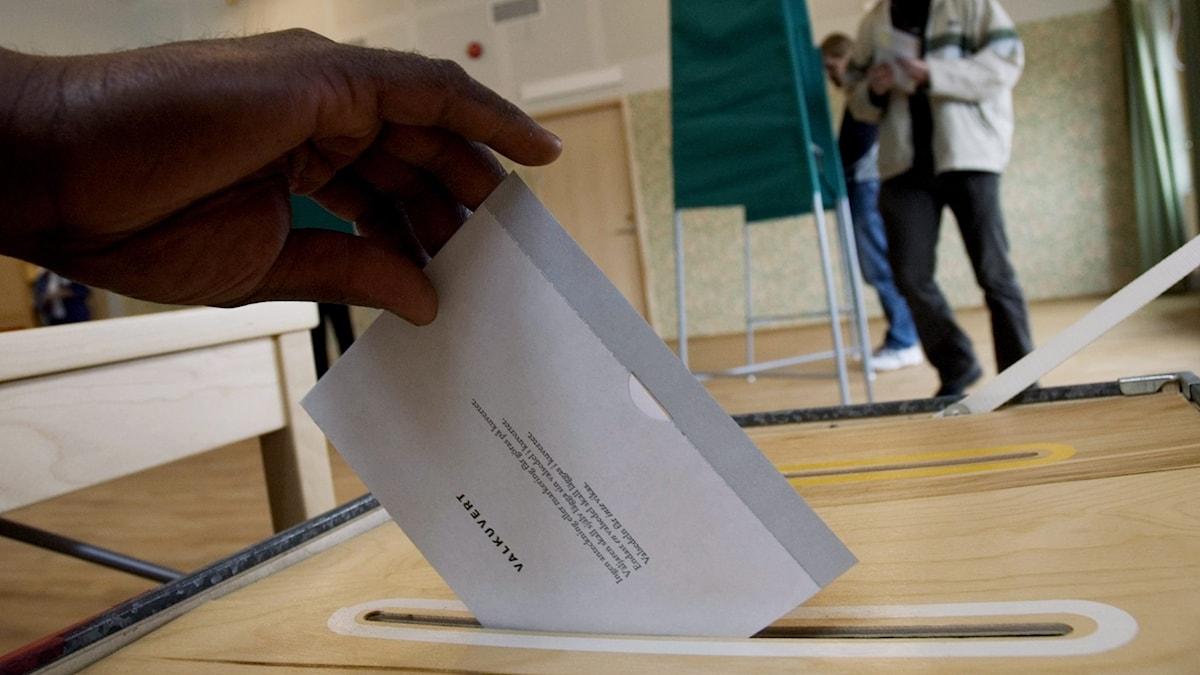 En hand lägger en valkuvert i valurnan. I bakgrunden syns personer vid valbås.