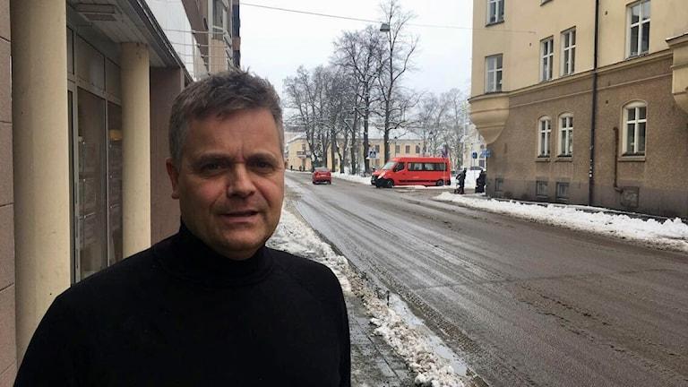 Henrik Holm i svart tröja står vid en snömoddig väg i centrala Jönköping.