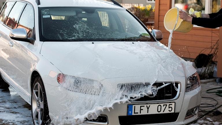 En person tvättar bilen på sin tomt.