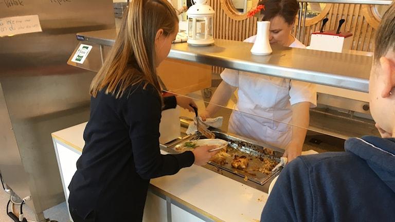 En elev tar mat i en skolmatsal.
